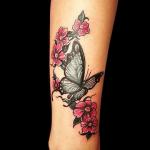 tatuaje de una mariposa con flores rosas en la pierna