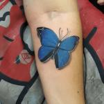 tatuaje de una mariposa de color azul en el antebrazo