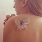 tatuaje de una mariposa blanca en el hombro