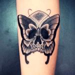 tatuaje de una mariposa con calavera hecho en el brazo