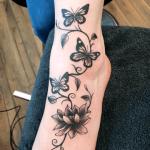 tatuaje de una mariposa con enredaderas en el pie