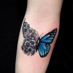 tatuaje de una mariposa azul que se transforma en flores negras