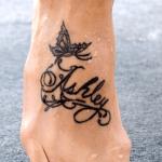 tatuaje de una mariposa con un nombre en el pie