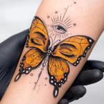 tatuaje de una mariposa de color amarilla con ojos