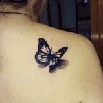tatuaje de una mariposa negra en 3d posada en el hombro