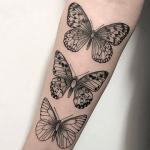 tatuaje de tres mariposas negras hechas en el brazo