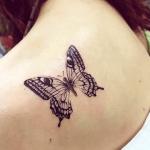 tatuaje de una mariposa negra en el hombro