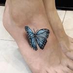 tatuaje de una mariposa azul en 3d en el pie