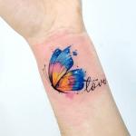 tatuaje de una mariposa colorida en la muñeca con una frase