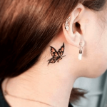 tatuaje de una mariposa naranja detrás de la oreja