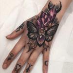 tatuaje de una mariposa gótica en la mano