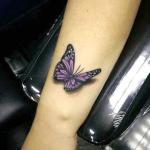 tatuaje de una mariposa de color morado o violeta en el brazo