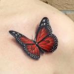 tatuaje de una mariposa de color rojo en el hombro