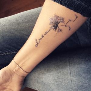 Tatuaje de diente de león con frase hecho en el antebrazo