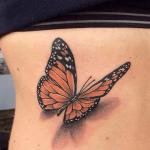tatuaje de una mariposa de color naranja en el costado