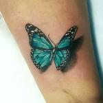 tatuaje de una mariposa en color verde en el brazo
